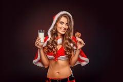 Natal e ano novo Mulher no traje de Santa com posição da capa isolado no preto com vidro do leite e da cookie foto de stock royalty free