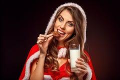 Natal e ano novo Mulher no traje de Santa com posição da capa isolado no sorriso de mordedura preto da cookie do leite bebendo foto de stock