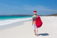 Natal em Austrália - mulher que anda ao longo da praia com festivo Imagens de Stock Royalty Free