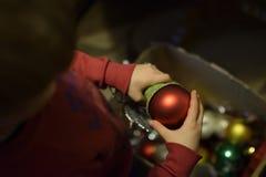 Natal em uma casa pobre A criança decora a árvore de Natal imagens de stock