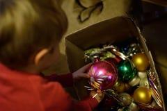 Natal em uma casa pobre A criança decora a árvore de Natal foto de stock royalty free