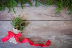 Natal Firbranch com cones, fita vermelha do às bolinhas no saco rústico no fundo de madeira velho foto de stock
