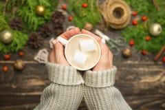 Natal, fundo do ano novo Liso-configuração, brinquedos de brilho, mãos fêmeas com uma caneca de latte quente com marshmallow, can imagem de stock royalty free