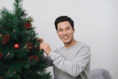 Natal Homem asiático que está o celebra novo da árvore de Natal em casa imagem de stock