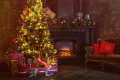 Natal interior árvore de incandescência mágica, chaminé, presentes na obscuridade na noite foto de stock royalty free