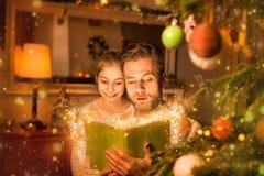 Natal - livro de leitura do pai e da filha em casa Fotografia de Stock Royalty Free