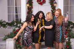 Natal, x-mas, ano novo, inverno, conceito da felicidade - quatro mulheres de sorriso olham o pulso de disparo ou o relógio Fotografia de Stock