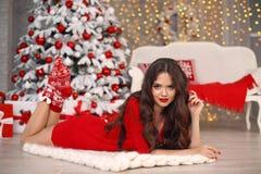 Natal Menina bonita de Santa Mulher de sorriso com cabelo longo e a composição vermelha dos bordos que encontram-se na cobertura  imagem de stock royalty free