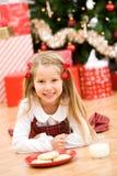 Natal: Menina com o petisco para a árvore de Santa In Front Of Christmas Fotografia de Stock Royalty Free
