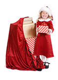 Natal: A menina está ao lado do saco de presentes do feriado fotografia de stock royalty free