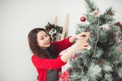Natal Mulher bonita asiática que está o ce novo da árvore do Xmas em casa fotografia de stock royalty free