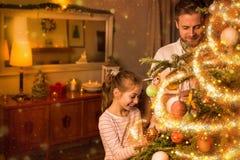 Natal - o pai e a filha decoram a árvore de Natal Imagens de Stock Royalty Free
