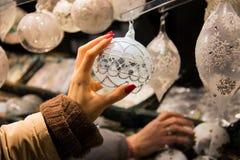 Natal que compra, mão bonita da mulher que alcança elegantemente após a decoração da bola na cor branca da pérola imagens de stock
