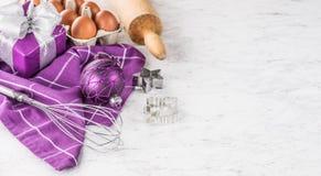 Natal que coze ovos das decorações dos presentes e o utensílio roxos da cozinha na tabela de mármore fotos de stock