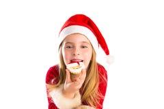 Natal Santa que come a menina loura da cookie e da criança do Xmas Fotografia de Stock