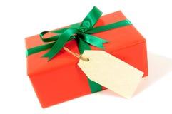 Natal vermelho pequeno ou presente de aniversário com a curva da fita, a etiqueta do presente ou a etiqueta verde, isolada no fun Fotografia de Stock Royalty Free
