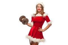 Natal, x-mas, inverno, conceito da felicidade - halterofilismo Mulher forte do ajuste que exercita com pesos no ajudante de Santa Fotos de Stock