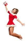 Natal, x-mas, inverno, conceito - mulher de sorriso no chapéu do ajudante de Santa com a caixa de presente, salto da felicidade p Fotos de Stock Royalty Free