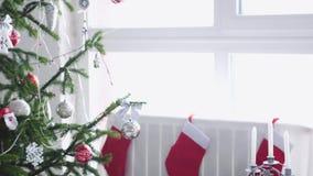 Natale bianco alla moda interno con l'albero di abete decorato, calzini, candele, ghirlanda dalla finestra archivi video