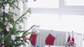 Natale bianco alla moda interno con l'albero di abete decorato, calzini, candele, ghirlanda, pattini di inverno dalla finestra le archivi video