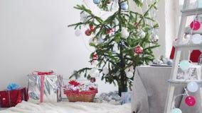 Natale bianco alla moda interno con l'albero di abete decorato, scala a libro, contenitori di regalo, candele dalla finestra Movi archivi video