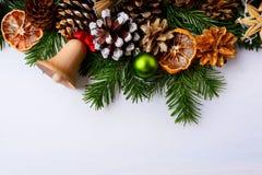 Natale che accoglie con la campana di tintinnio, le arance secche ed il Orn verde Fotografia Stock Libera da Diritti