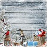 Natale che accoglie fondo con il pupazzo di neve, i regali, i rami del pino e le decorazioni di Natale Fotografie Stock