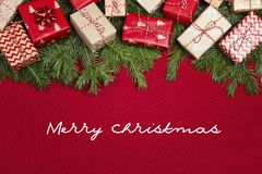 Natale che accoglie messaggio con i rami ed i regali dell'abete sul fondo rosso del panno immagini stock