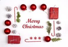 Natale che accoglie messaggio con le decorazioni ed i regali su fondo bianco immagini stock