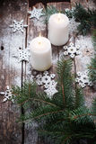 Natale che brucia le candele con i fiocchi di neve, albero di abete verde su fondo di legno Immagine Stock
