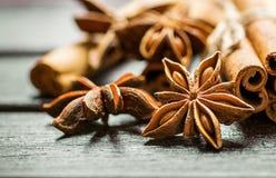 Natale che cuoce i bastoni di cannella degli ingredienti Anise Star Cloves Cardamom Scattered su fondo di legno fotografia stock libera da diritti