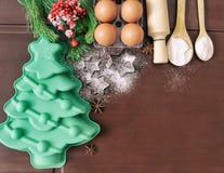 Natale che cuoce il fondo del dolce Ingredienti e strumenti per cuocere - farina, uova, muffe del silicone sotto forma di un albe fotografie stock