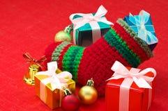 Natale che immagazzinano e presente variopinti sul fa rosso Fotografia Stock