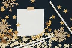 Natale che progetta derisione di concetto su Nota su fondo nero con nastro adesivo di washi, i coriandoli delle stelle d'oro, la  Immagini Stock