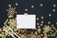 Natale che progetta derisione di concetto su Nota su fondo nero con nastro adesivo di washi, i coriandoli delle stelle d'oro, la  Fotografia Stock Libera da Diritti