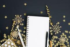 Natale che progetta derisione di concetto su Taccuino su fondo nero con le stelle d'oro coriandoli, regalo, serpentina e fiocchi  Fotografia Stock Libera da Diritti