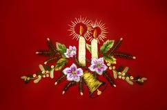 Natale con le candele brucianti, campana e fiori, ricamati su fondo rosso Fotografie Stock