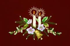Natale con le candele brucianti ed i rami dell'abete con i fiori su fondo vinoso Immagini Stock