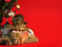Natale Contenitore di regalo sotto l'albero di Natale sopra fondo rosso Fotografie Stock