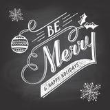 Natale dell'A mano iscrizione che accoglie etichetta sulla lavagna Fotografia Stock Libera da Diritti
