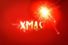 Natale di parola con le scintille su fondo rosso Immagine Stock Libera da Diritti