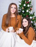 Natale e concetto di amicizia - ragazze che parlano e che bevono il co Immagini Stock