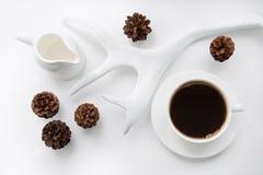 Natale e concetto di inverno Tazza di caffè nero e dei coni caldi, corni su fondo bianco Vista superiore Scheda di festa Immagine Stock Libera da Diritti