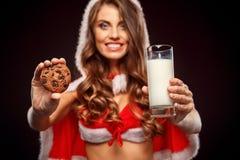 Natale e nuovo anno La donna in costume di Santa con la condizione del cappuccio isolato sul nero con bicchiere di latte ed i bis immagine stock