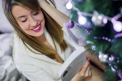Natale, feste e concetto della gente - libro di lettura felice della giovane donna a casa fotografie stock libere da diritti