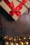 Natale fondo, contenitore di regalo e palle di legno dell'oro Fotografia Stock