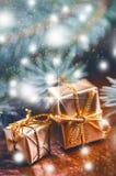 Natale fondo, regali e rami attillati Regali di Natale su un fondo di legno Fuoco molle Scintille e bolle Abst Fotografie Stock
