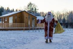 Natale, freddo, dicembre Santa Claus che va con una borsa dei regali nell'inverno sul campo innevato fotografia stock