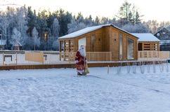 Natale, freddo, dicembre Santa Claus che va con una borsa dei regali nell'inverno sul campo innevato immagini stock libere da diritti