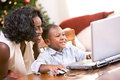 Natale: Il ragazzo d'aiuto della madre scrive Santa Letter On Computer Immagine Stock